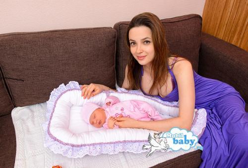 новорожденный в детском гнездышке и счастливая мама